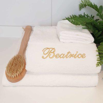 Vit handduk med namn och guldtext. Handduk med egen