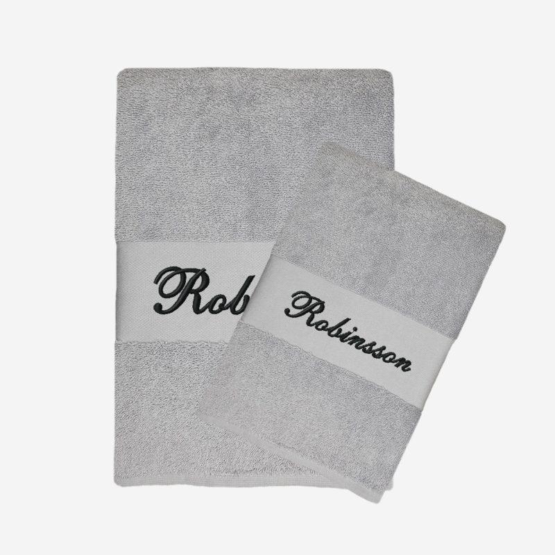 Grå handduk med namn och svart text