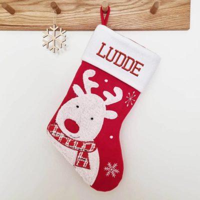 Röd och vit julstrumpa med namn. motiv ren